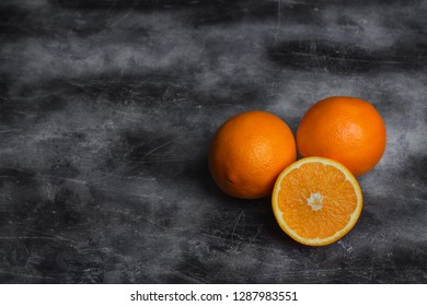 Oranges lying on a dark background. Free space for text. Ripe, juicy citrus fruit.