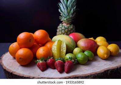 Oranges, mangos,papaya,strawberry, pineapple, limes and lemons arranged on wooden disk