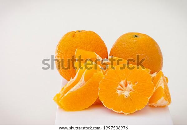 Oranges, peeled and sliced on white background