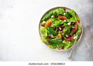 Oranges, pomegranate seeds and mixed salad leaves fresh salad on gray stone background. Flat lay. Copy space