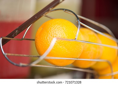 Oranges stacked in a metal holder to be squeezed into fresh juice