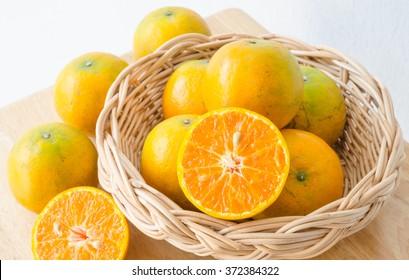 Oranges in a wicker basket on wooden table