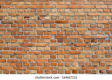 Orangey red face brick wall background texture of unpainted clay bricks in a repeat pattern in neat rows