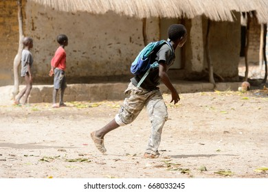 ORANGO ISLAND, GUINEA BISSAU - MAY 3, 2017: Unidentified local little boy with backpack walks along the street in the Etigoca village. People in G.-Bissau suffer of poverty due to the bad economy