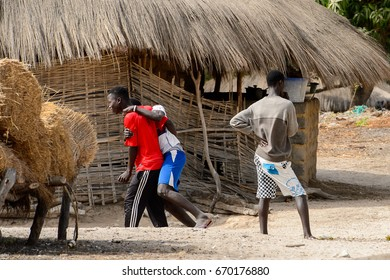 ORANGO ISLAND, GUINEA BISSAU - MAY 3, 2017: Unidentified local boys walk along the street in the Etigoca village. People in G.-Bissau suffer of poverty due to the bad economy