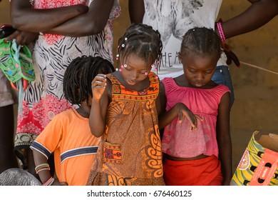 ORANGO ISLAND, GUINEA BISSAU - MAY 3, 2017: Unidentified local little girls with braids look down in the Etigoca village. People in G.-Bissau still suffer poverty