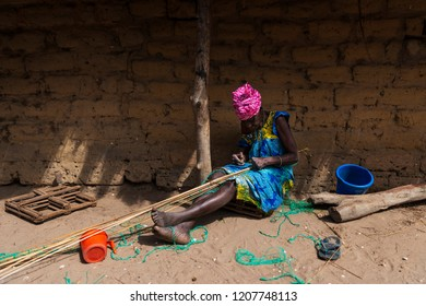 Orango Island, Guinea-Bissau - February 3, 2018: An old woman working in front of her hut at the village of Eticoga in the island of Orango.