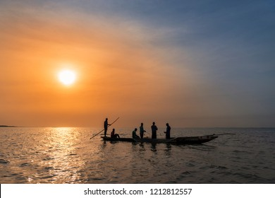 Orango Island, Guinea-Bissau - February 3, 2018:  Fishermen collecting the nets in an old traditional fishing canoe near the island of Orango at sunset.