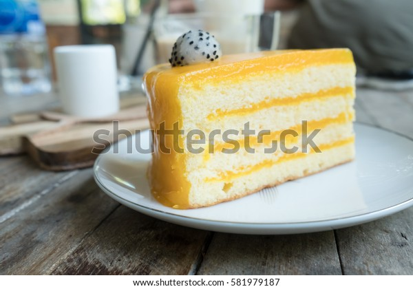 OrangOrange cake and coffee on wood table in coffee shop.e cake and coffee on wood table in coffee shop.