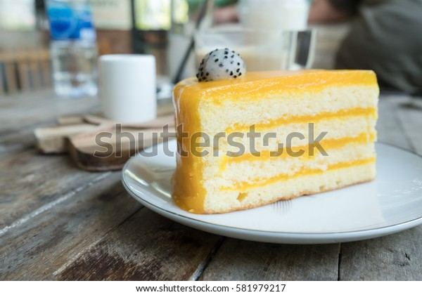 OrangOrange cake and coffee on wood table in coffee shop.e cake and coffee on wood table in coffee shop.