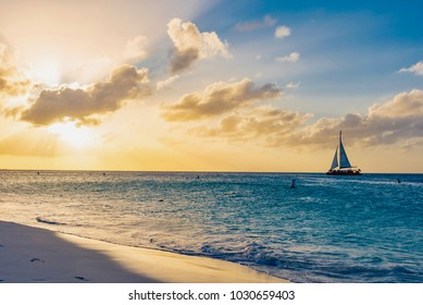 Oranjestad, Aruba - January 10 2018: sailing boats on the ocean and tourists at sunset of the Caribbeans on the island of Aruba in the Netherlands Antilles in winter
