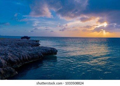 Oranjestad, Aruba - January 10 2018:   car parked on the Rocks in the wild coast at sunset in the Caribbean sea on the island of Aruba