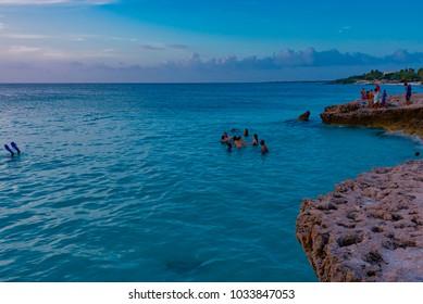 Oranjestad, Aruba - January 10 2018:   people in the lagoon swimming and having fun at sunset in the Caribbean sea on the island of Aruba