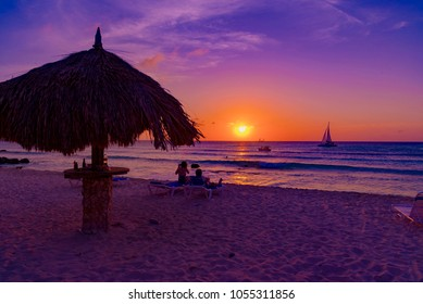 Oranjestad, Aruba - January 12 2018:  bright and colorful sunset on the Caribbean beach in Aruba island in winter with people on the white beach and palm trees