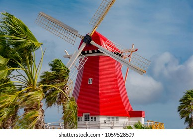 Oranjestad, Aruba - January 12 2018:   red Dutch windmill, with palm trees and blue skies on the island of Antilles Oalndesi antilles