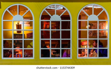 Oranjestad, Aruba - January 13, 2018: The window of a restaurant in the colorful center of Oranjestad with some people doing dinner