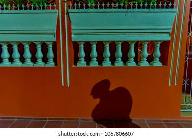 Oranjestad, Aruba - January 15 2018: night alley of the city of Oranjestad island of Aruba with shadow of man walking in the sidewalk