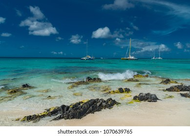 Oranjestad, Aruba - January 15 2018: panorama of the most beautiful beach of the Caribbean on the island of Aruba in the Netherlands Antilles with white sand palm trees and azure ocean with sailboats