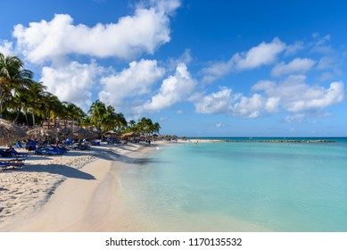 Oranjestad, Aruba - January 15, 2018: View of the turquoise water and the idyllic Eagle Beach in Aruba with tourists relaxing near the shore.