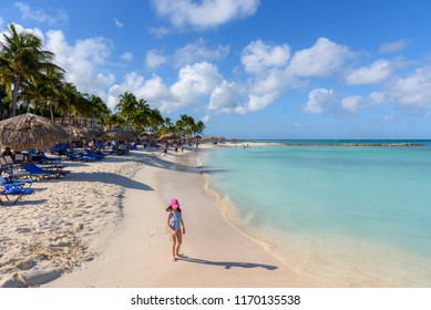 Oranjestad, Aruba - January 15, 2018: View of the turquoise water and the idyllic Eagle Beach in Aruba with a little girl walking on the shore