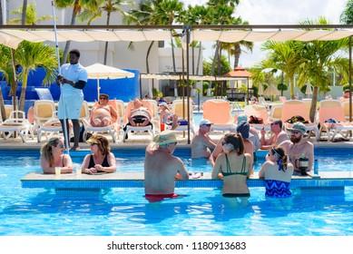Oranjestad, Aruba - January 15, 2018: People chat and have fun in a swimming pool in a resort of Aruba