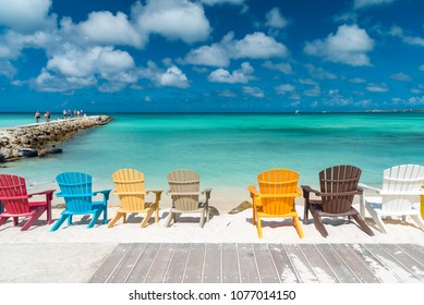 Oranjestad, Aruba - January 16 2018: colorful wooden chairs on the tropical Caribbean beach of the island of Aruba surrounded by palm trees for winter relaxation