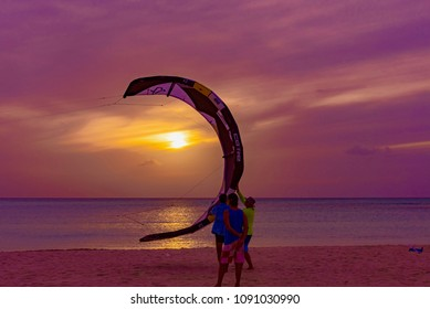 Oranjestad, Aruba - January 16 2018:    Kitesurfing at sunset in the tropical beach of the Caribbean Island of Aruba