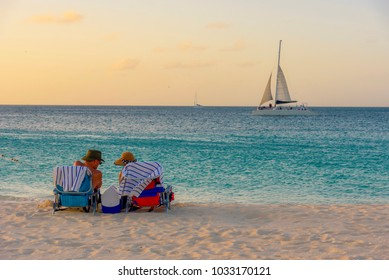 Oranjestad, Aruba - January 7, 2018: A couple relax and have fun in the famous Eagle Beach in Aruba at sunset with a boat at the horizon.