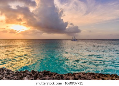Oranjestad, Aruba- January 7, 2018: Tropical seascape with a boat at the horizon at sunset in Boca Catalina, an idyllic beach of Aruba.