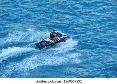 Oranjestad, Aruba - November 17, 2018 - A guy on a jetski speeding on the bay