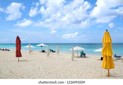 Oranjestad, Aruba. Unrecognizable People Walking Along White Sands at Eagle Beach. Dramatic Clouds