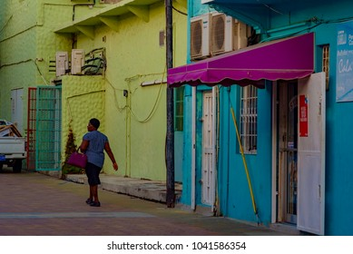 Oranjestad,Aruba - January 10 2018: woman walking in the center of the colorful and vibrant city of Oranjestad, the capital of Caribbean island of Aruba