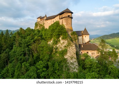 Orava castle - Oravsky Hrad in Oravsky Podzamok in Slovakia. Medieval stronghold on extremely high and steep cliff. Aerial view in summer at sunset