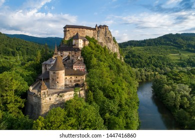 Orava castle - Oravsky Hrad in Oravsky Podzamok in Slovakia. Medieval stronghold on extremely high and steep cliff by the Orava river. Aerial view in sunrise light in summer