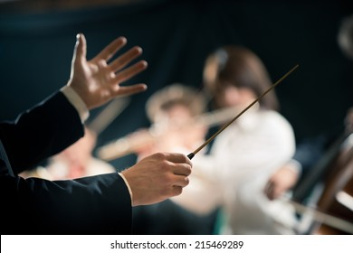 Orchestra conductor directing symphony orchestra with performers on background, hands close-up.