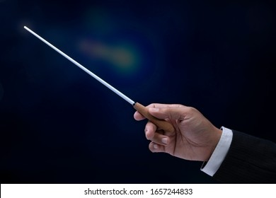 Orchestra conductor hands baton. Hands of conductor holding stick on a black background