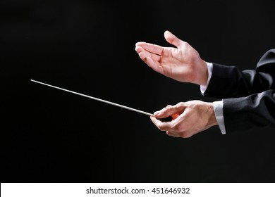 Orchestra conductor hands on black background