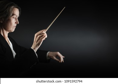 Orchestra conductor music conducting. Woman leader Maestro hands with baton