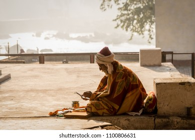 ORCHHA, INDIA - JANUARY 30, 2015: A Sadhu in morning light by the Betwa River at Orchha in the state of Madhya Pradesh in central India.
