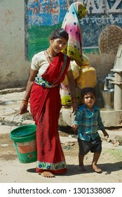 Orchha, India - March 27, 2007: Unidentified young woman with a child carries plastic bucket with water at the street in Orchha, India.