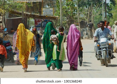 Orchha, India - March 27, 2007: Unidentified Indian women wearing colorful sarees walk by the street in Orchha, India.