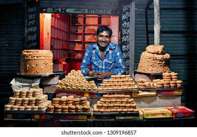 Orchha, India – November 30, 2018: Portrait of unidentified Indian man on nights market with milk sweetness of Barfi. Daily lifestyle in rural area central India.
