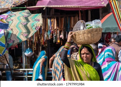 Orchha, Madhya Pradesh, India - March 2019: An Indian woman carrying a wooden basket with steel utensils on her head in the colourful market in the city of Orchha.