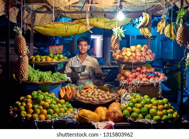 Orchha, Madhya Pradesh, India - November 30, 2018: Portrait of unidentified Indian man on night market with fruits. Daily lifestyle in rural area central India.