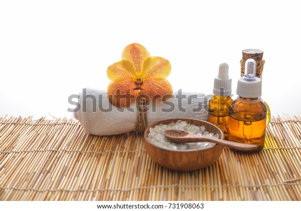 orchid with bottle oil ,rolled towel ,salt,spoon in bowl on bamboo mat