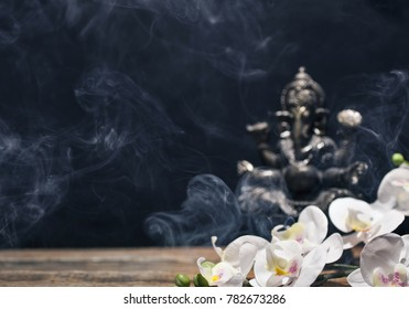 Orchid flowers and hindu god Ganesh on black background. Statue on wooden table with a smoke of incense. Copy space.