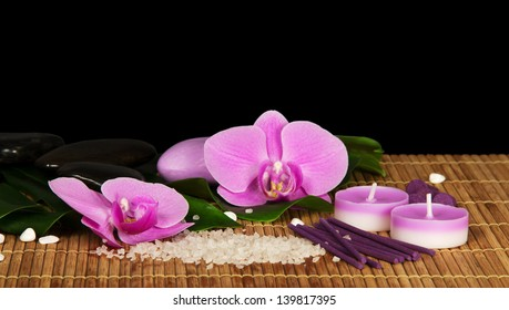 Orchid flowers, set for Spa on the bamboo cloth, isolated on black