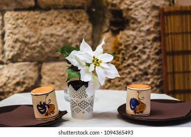 An orchid in the middle of a table set up outside and with two plates and two glasses of earthenware.
