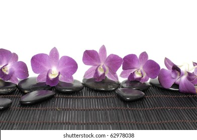 Orchid on massage stones on bamboo stick straw mat