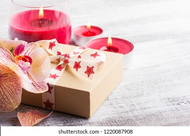 Orchids, craft gift box and lit candles candles on a blue background